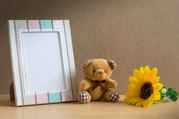 Bear doll with photo frame and sunflower.