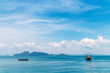 blue sea and sky with white cloud, fishing boat and mountain in background