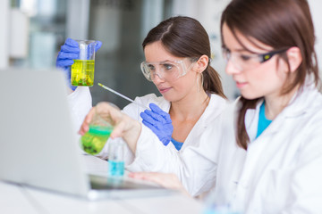 Two young female researchers carrying out experiments in a lab