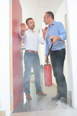 men sets a fire extinguisher at the office