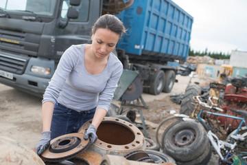 woman mechanic picking axle in car scrap yard
