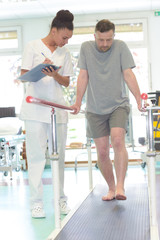 male patient standing with a physiotherapist