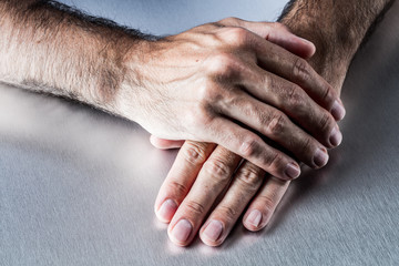male hands relaxing on each other flat waiting or listening