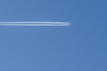 Airplane with condensation trails on blue sky
