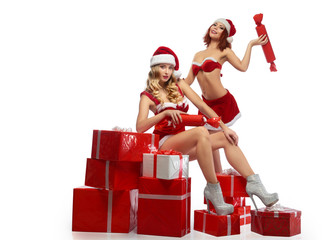 Two sexy Christmas girls posing with a pile of presents