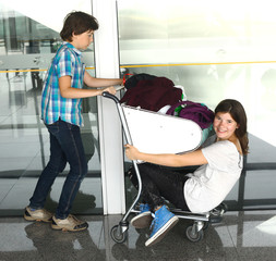 teen kids in the airport with trolley close up photo
