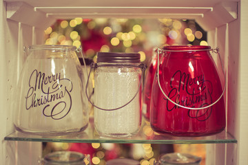 Three glass candle holders jars in the box, selective focus, with beautiful bokeh on the background