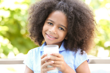 Pretty African-American girl with a glass of milk in the garden