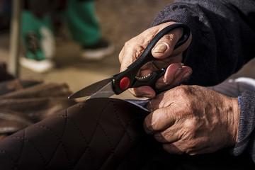 Artesano ambulante tapicero midiendo y cortando.