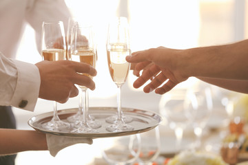 Hands taking glasses with champagne from metal tray, close up view