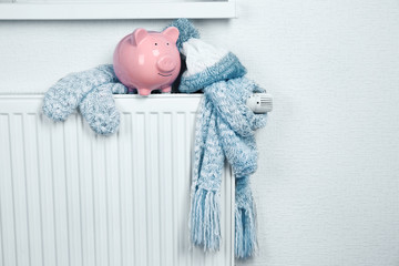 Heating radiator with piggy bank and warm clothes indoor