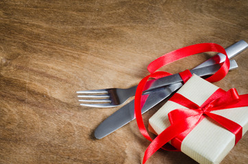 Present and Cutlery Decorated with Red Ribbon on Wooden Background.