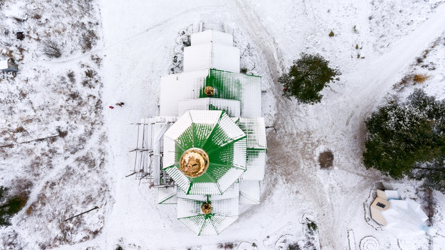 Green roof of church with golden dome and cross covered with snow. Top view. Winter