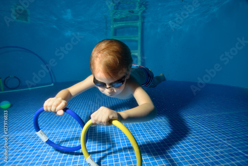 The Child Swims And Trains Underwater In The Pool And Picking Up