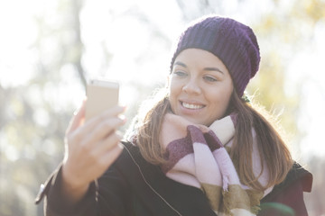 A young woman is photographed on a mobile phone, Selective focus and small depth of field, lens flare