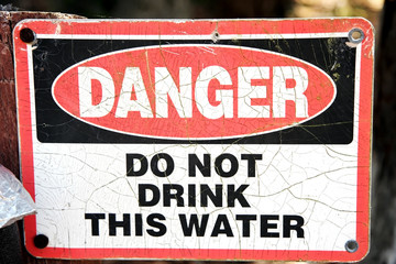 Faded and weathered Danger Don't Drink This Water sign. Horizontal.