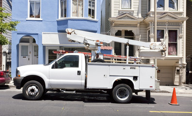 Parked utility truck with cherry picker truck. Horizontal.