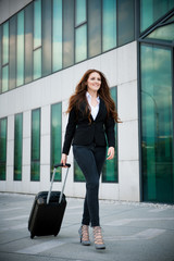 Business travel - woman with suitcase walks outside airport buil