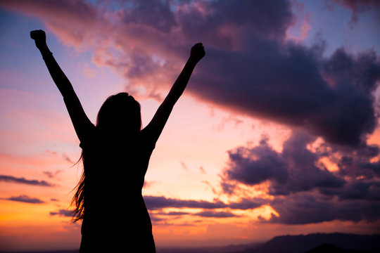 woman gesturing success - silhouette over evening sky