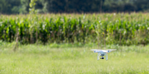 Quadcopter drone flying over a cultivated field