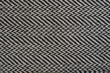 Herringbone (Broken Twill Weave) - a distinctive V-shaped weaving pattern. Closeup. Grey textured background.