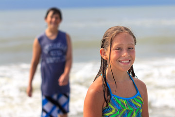young girl smiling at camera as her brother watches in the surf at the beach
