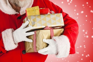 Composite image of santa claus holding gifts
