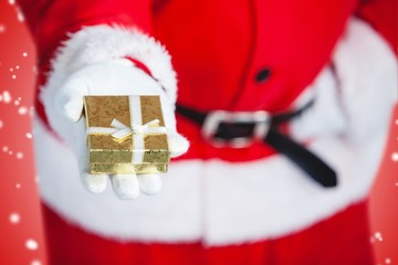 Composite image of santa claus holding a gift box in hand