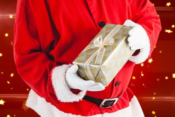 Composite image of santa claus holding gift box