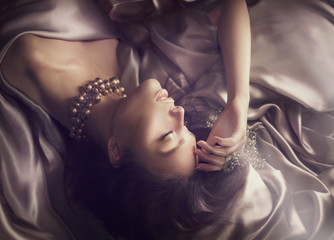 Sexy beautiful brunette woman lying in bed. Woman sleeping in dark room