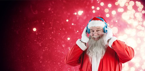 Composite image of portrait of santa claus listening to music on