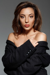 Young beautiful woman looking at  camera over grey background.
