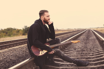 Handsome man with guitar sitting on railroad