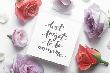 """Inscription """"DON'T FORGET TO BE AWESOME"""" written on paper with flowers on white background"""