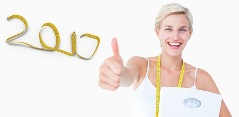 Composite image of happy woman holding scales with thumbs up