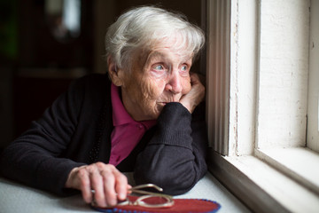An elderly woman looks sadly out the window.