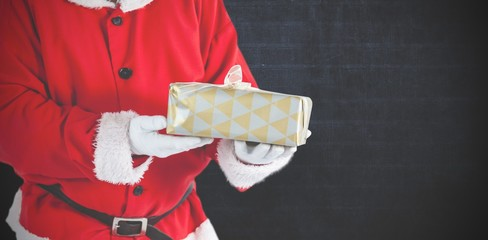 Composite image of santa claus holding a gift box