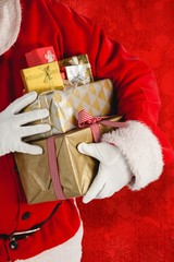 Composite image of santa claus holding presents