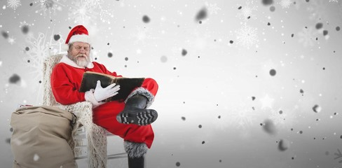 Composite image of santa claus reading bible with sack of christ