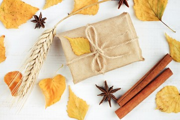 Autumn handcraft gift box with dried leaves adornment. Fall time welcoming congratulation. Simple autumn decoration idea.
