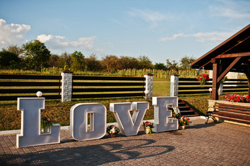 Great big letter word LOVE with light inside at wedding ceremony