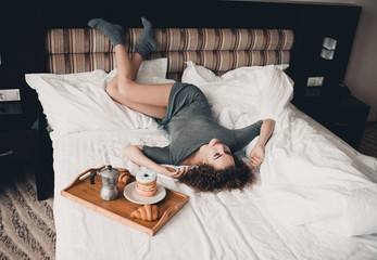 Beautiful young girl 20-24 year old lying with breakfast in bed. Good morning.