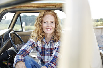 Portrait of smiling woman sitting in pick up truck