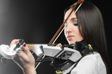 Woman playing the violin on a black background