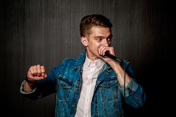 Young Guy in Jeans Jacket Beat Boxing with Microphone in Studio. Singer Beatboxing Performance. Concert and Beat Box Music Concept. Dark Background. Toned Photo.