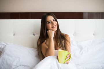 attractive young woman drinking coffee while sitting in bed