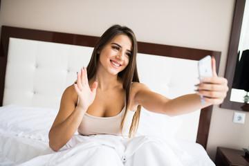 Beautiful girl making selfie in the bed