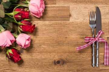 Wooden table with roses, knife and fork. Valentines day background