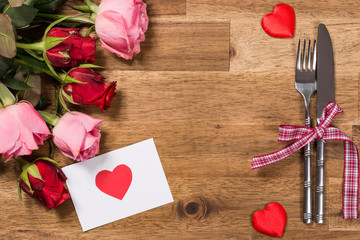 Flowers, silverware, greeting card on wooden table. Valentines day background