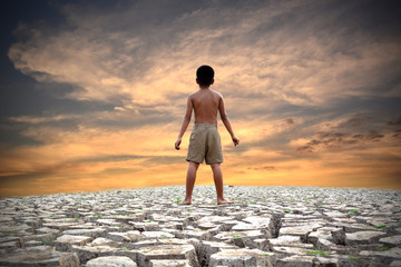Sad a boy stand on dry ground .concept drought and hope
